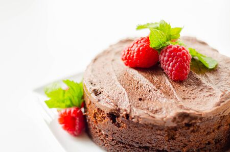 Gluten free tasty round cake based on Belgian chocolate decorated with fresh raspberries and mint, delicious sweets