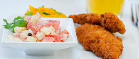 Breaded and herbed chicken fillet served with mashed carrots with potatoes and tomato salad with onions, tasty food