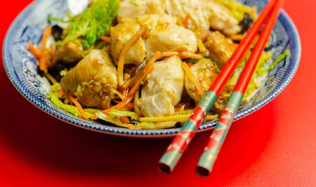 Cooked chicken pieces with savory garlic and ginger soy sauce and noodles, black fungus mushrooms, savoy cabbage, and carrot, Chinese food