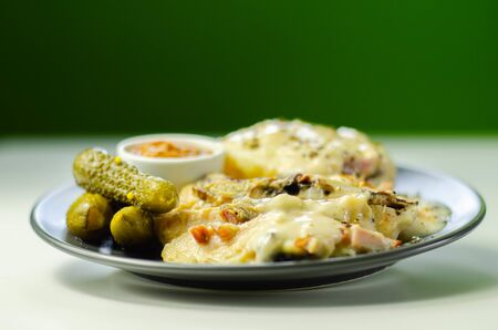 Chicken with sliced mushrooms, ham, in cheese sauce with mash potato, pickled red cabbage, and gherkin, tasty food