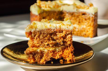 Geschnittener Karottenkuchen gefüllt und belegt mit Frischkäse-Buttercreme und dekoriert mit Walnüssen, Bäckerei
