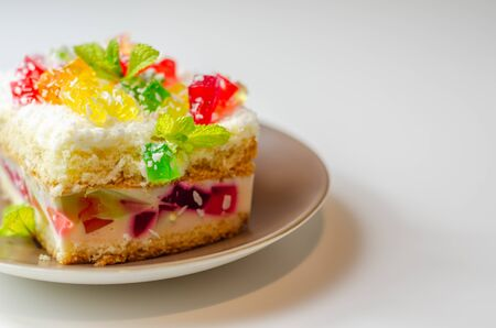 A portion of cream cake with pieces of colorful jelly and sprinkled with coconut flakes, party cake