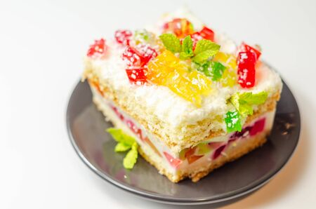 A portion of cream cake with pieces of colorful jelly and sprinkled with coconut flakes, party cake Reklamní fotografie