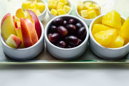 Various set fruits, pineapple, apple, grapes with matured cheddar cheese in bowls, healthy snack
