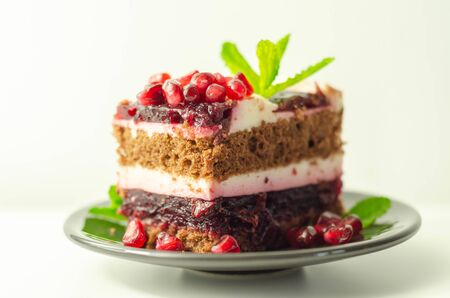Colorful multi-layered cream chocolate cake with cherry jam and pomegranate, a delicious treat