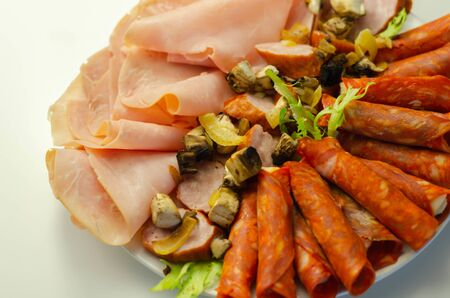 A cold plate prepared for the party with sliced chorizo, ham and sausages, a set of cold cuts