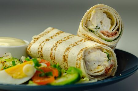 Tortilla wrap with chicken and beechwood smoked bacon served with mix salad on the blue plate, tasty food