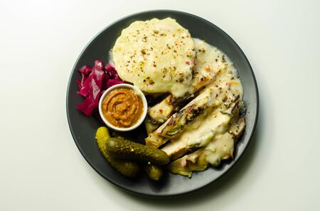 Chicken breast with sliced mushrooms, ham, in cheese sauce with mash potato, pickled red cabbage, and gherkin, tasty food Imagens