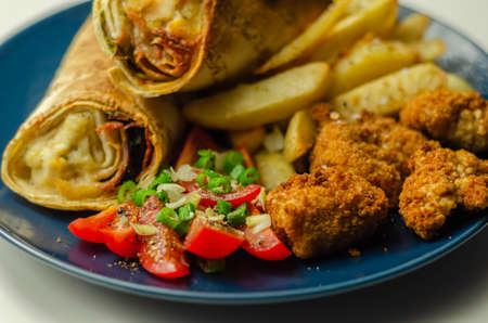 Tortilla wrap with chicken and beechwood smoked bacon served with chicken nuggets and chips, tasty food Banque d'images
