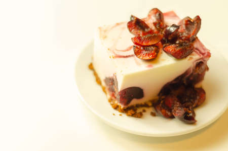 Japanese cheesecake with cherry sauce and fresh cherries on the ceramic plate and red background, sweet dessert