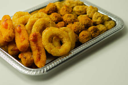 Southern fried and roast chicken bites, onion rings and mozzarella stick served on the silver tray, party bites