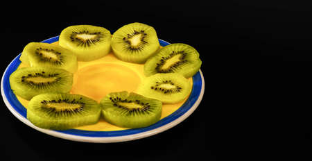 Fresh and juicy sliced kiwi served on a yellow blue plate, tasty fruits Banque d'images