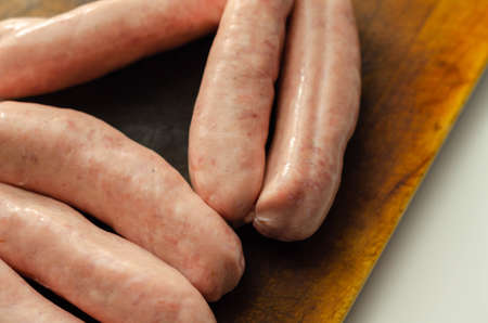 Raw classic British sausage made from prime cuts of pork on the wooden board, prime pork sausages