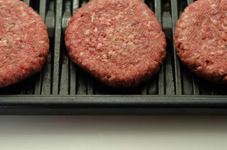 Seasoned beef burgers with a pinch of salt and black pepper on the grill, cookout Banque d'images