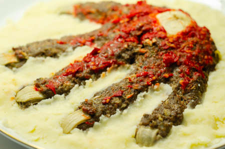 Roasted minced meat formed in the shape of a hand, topped with a tomato and pepper sauce, a creative way of serving food for Halloween, scary food Banque d'images