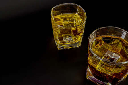 Two glasses with scotch whiskey and ice cubes on black background, relax time
