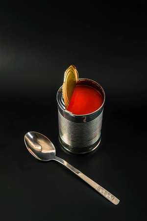 Delicious tomato soup in an open metal can with a spoon on a black background, a simple and tasty meal