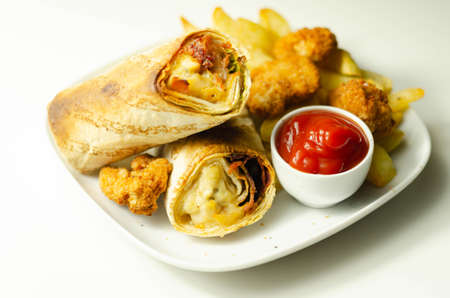 Tortilla wrap with chicken and beechwood smoked bacon served with chicken nuggets and chips on the white plate, tasty food