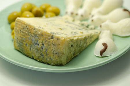 Full fat soft blue veined cheese with olives and snacks in the shape of mice, funny food