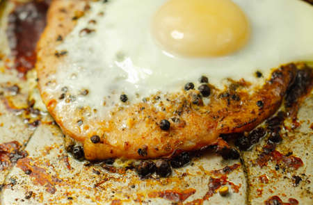 Fried portion of gammon served with egg on the metal plate, english meal