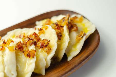 Close up of dumplings sprinkled with fried onion, traditional Polish, Russian and Ukrainian cuisine, tasty dish
