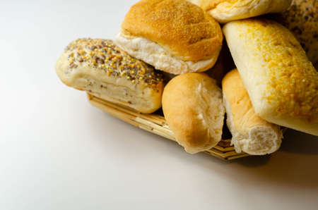 Various types of bread served on a wicker tray, delicious and fresh rolls, morning food