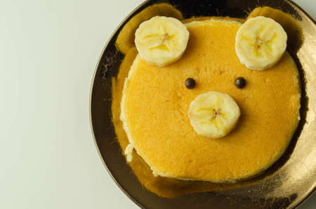 Creative meal for a child, pancake with banana and chocolate  in a face little bear  shape, funny food