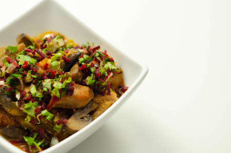 A thick stew of meat, potatoes, mushrooms, and mix of peppers served in a white bowl, delicious meal
