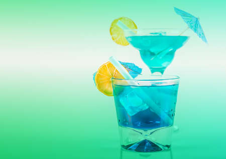 Two different blue cocktails with lemon and ice cubes, refreshing alcoholic drinks based on vodka and blue liqueur Banque d'images