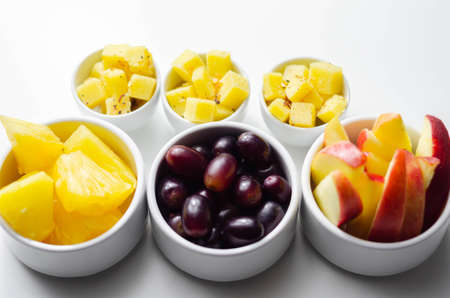 Various set fruits, pineapple, apple, grapes with matured cheddar cheese in bowls, healthy snack Banque d'images