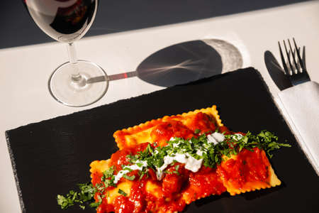 Four cheese filled ravioli in a tomato and basil sauce on the black stone plate, a famous dish from the French city of Nice