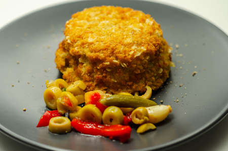 Cod and prawns red Thai style fish cake served with pickled olives, gherkin, garlic, and red peppers, Asian food