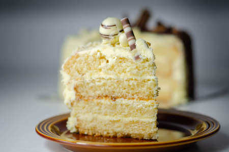 A piece of layered white cream cake with confectionery decorations, dessert for the celebration