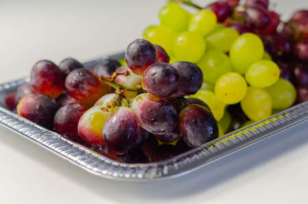 Three types of green, red and black grapes on a silver tray, fresh fruits