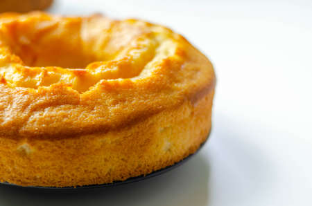 Freshly made madeira ring loaf cake decorated on white background, traditional cake