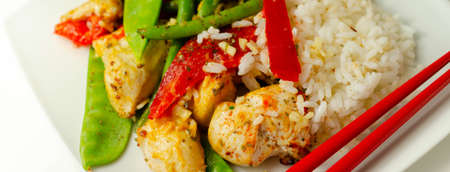 Chicken breast pieces in a Thai red curry sauce made with coconut cream, red chillies, lemongrass, lime leaf, with fragrant rice, red peppers, mange tout, and green beans, Thai food