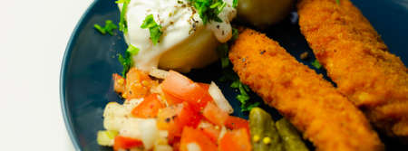 Breaded and herbed chicken breast fillet served with mashed potatoes,  tomato salad with onions and gherkin, tasty food