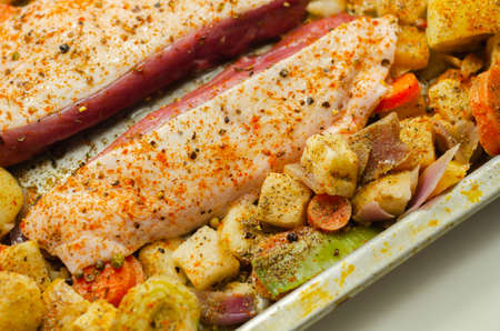 Raw duck breast with vegetables prepared on a metal baking tray, tasty food