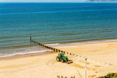 A tractor moving sand on an English beach on a sunny day in the background beautiful ocean, coastal industry