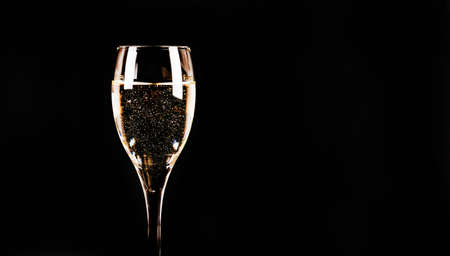 Expensive and luxurious vintage champagne with delicate bubbles in a wine glass on a black background, exclusive drink Foto de archivo