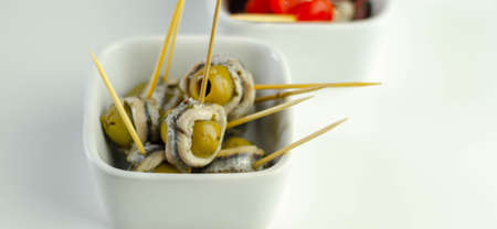 The traditional Spanish appetizers of olives, tomatoes and anchovies in a white ceramic bowls, seafood 版權商用圖片