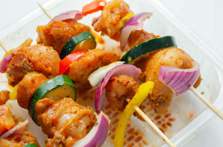 Raw skewers with chicken, zucchini, mushrooms, peppers and onions prepared for grilling, party food