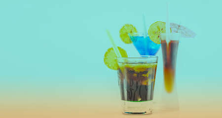 Three different colorful cocktails with lemon and ice cubes, refreshing alcoholic drinks 版權商用圖片