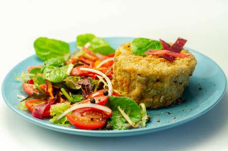 Smoked haddock fishcake with melting cheddar sauce and mixed salad on the blue plate, seafood 版權商用圖片