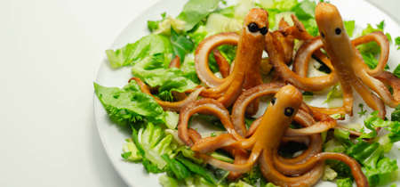 Creative meal for a child, fried sausages in an octopus shape served with fresh gem lettuce, funny food