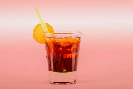 Delicious cocktail in drink glass with lemon and ice cubes, a sweet alcoholic drink based on rum and cola, party time