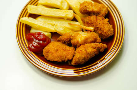 Chicken breast chunks, coated in breadcrumbs with potato chips and ketchup, tasty food