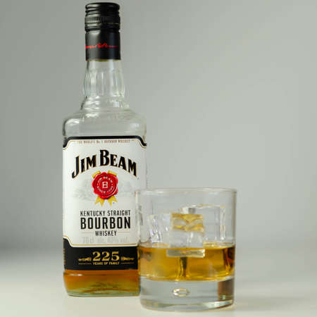 LONDON, UNITED KINGDOM - AUGUST 04, 2020 Straight bourbon whiskey by Jim Beam in a whiskey glass and a bottle commemorating 225 years of the Jim Beam family 新聞圖片