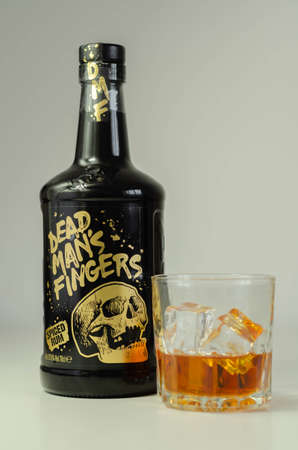 LONDON, UNITED KINGDOM - AUGUST 04, 2020 Interesting spiced blended rum from St. Ives in Cornwall served in a glass, in the background a characteristic bottle with a skull image