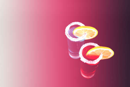 Mixed drinks in shot glasses with sliced lemon prepared by the bartender, party night